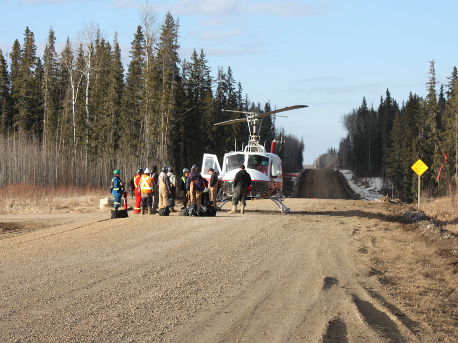 Delta Helicopters Bell 204B helicopter picks up forestry crew from dirt road in Northern Alberta