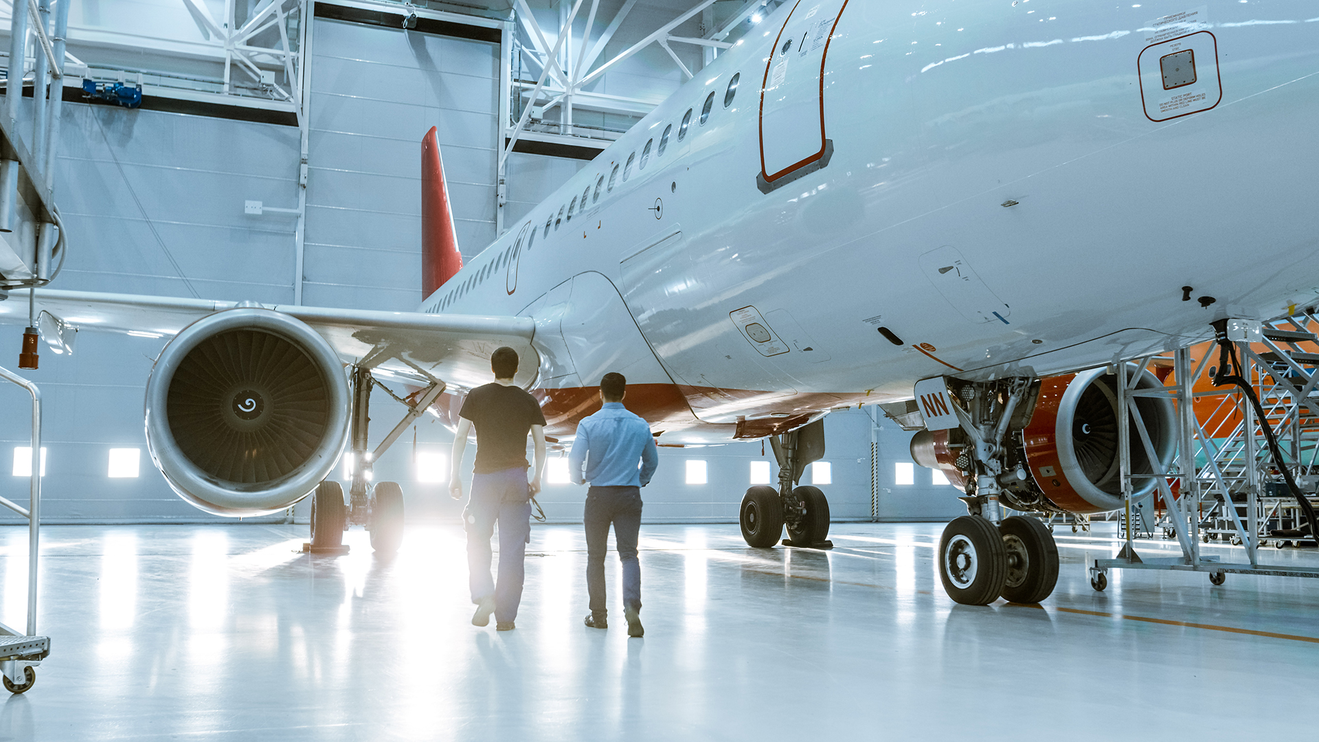 Aircraft mechanics and aircraft in hangar