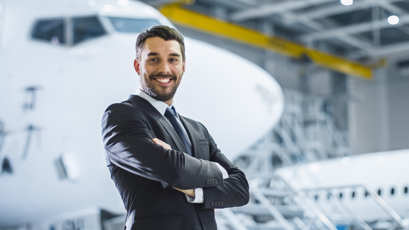 Business Owner stands next to aircraft in hangar