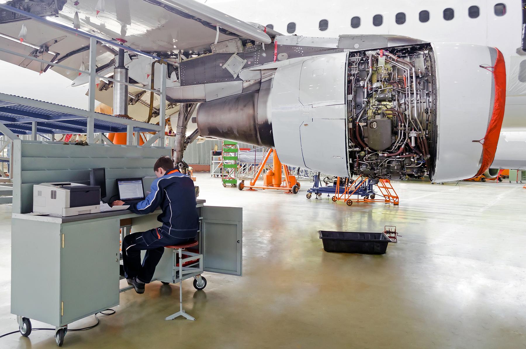 Aircraft Maintenance Technician at a Workstation in a Maintenance Hangar