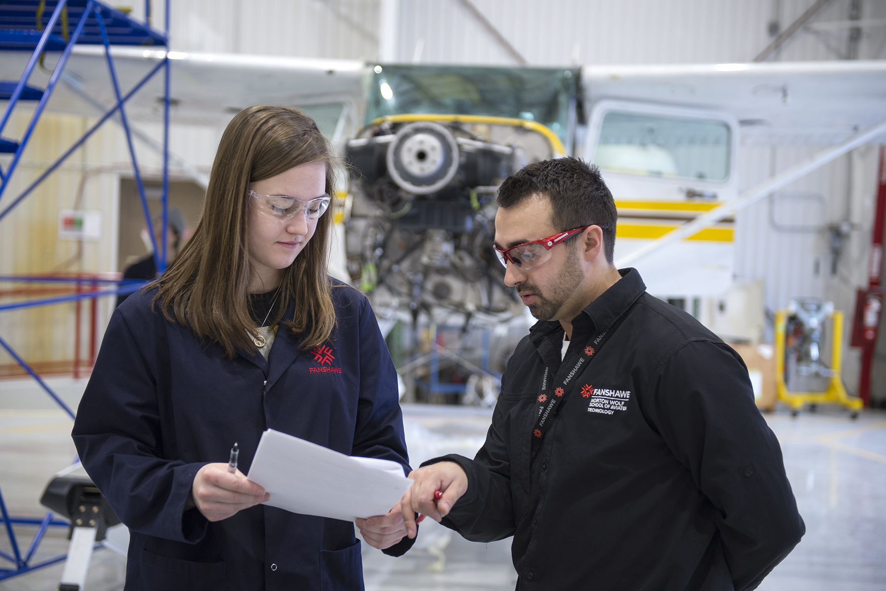 A student and instructor review documents at Fanshawe College's maintenance hangar