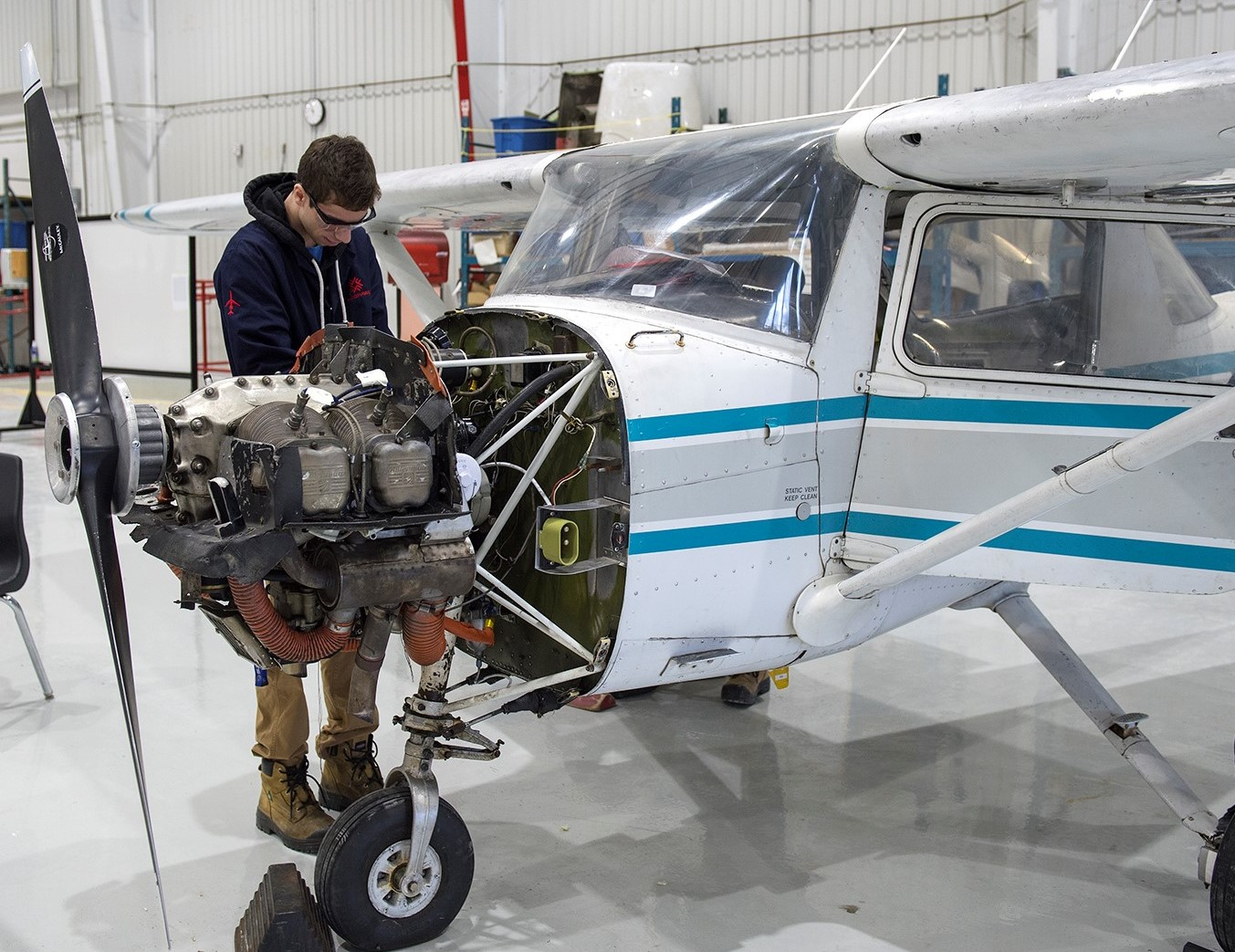 A student and instructor review documents at the maintenance hangar