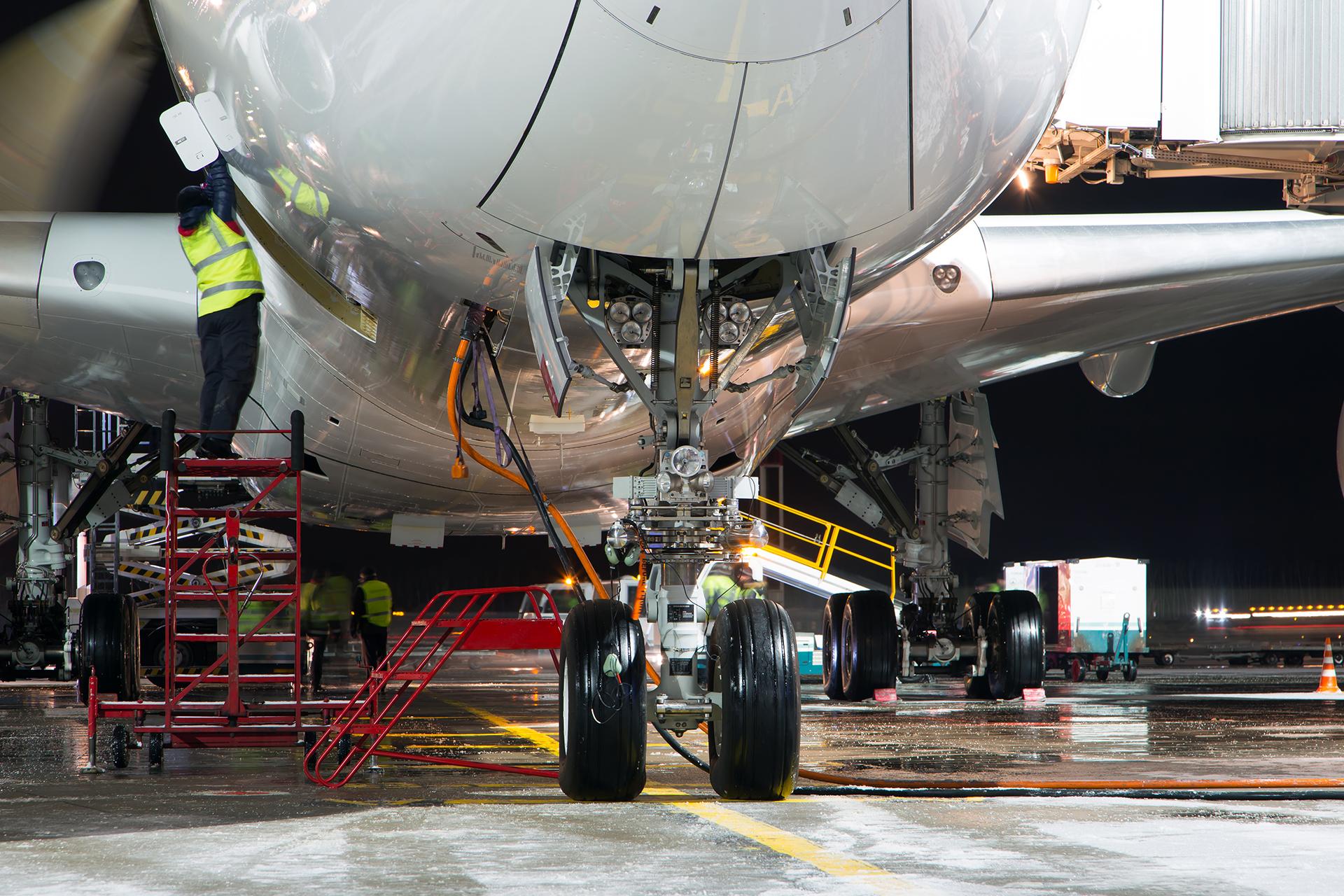 Staff perform maintenance on an aircraft at night